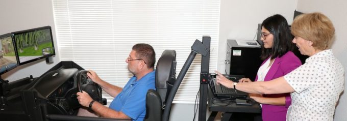 Instructor and student evaluating a client using a driving simulator